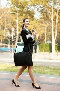 A woman in business attire walking gleefully in a park