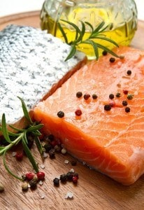 A piece of salmon and a piece of some other fish, with a few pieces of pepper on top.