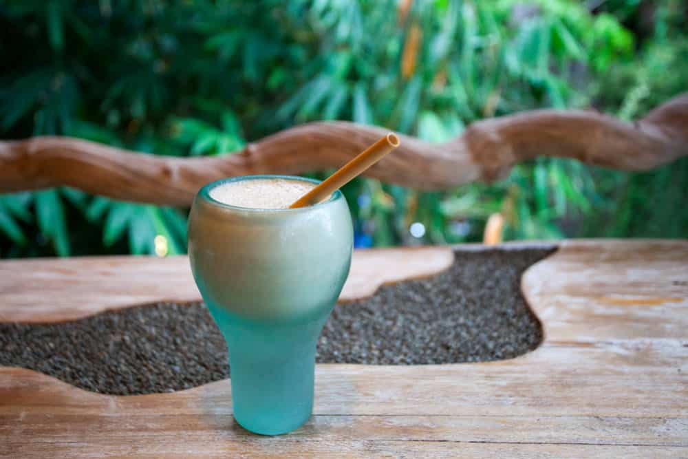 A glass of banana milk drink in front of a tropical background.