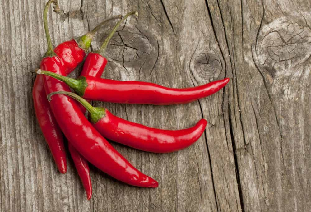 A bunch of red chili peppers on a rustic wooden surface.