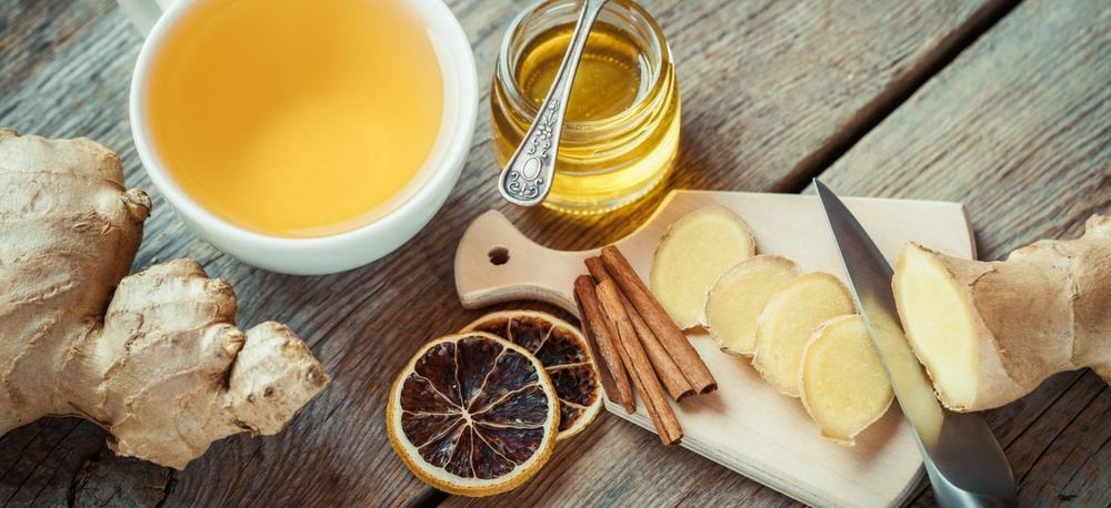 Ginger tea with dried lemond slices, a jar of honey, and cinnamon sticks.