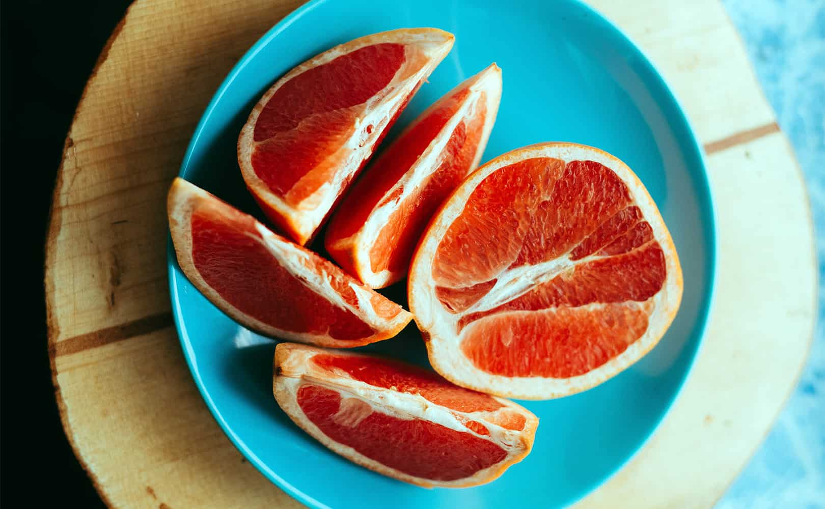 Sliced grapefruit on a blue plate, on a wooden table.