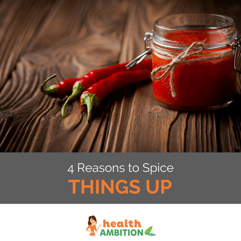 "Two chili peppers on a wooden surface next to a jar of chili sauce. The caption says ""4 Reasons to Spice Things Up."""