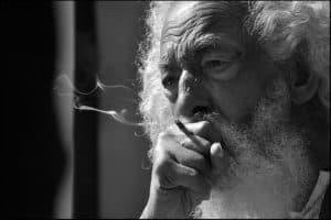 Blakc and white image of an old man smoking a cigarette.