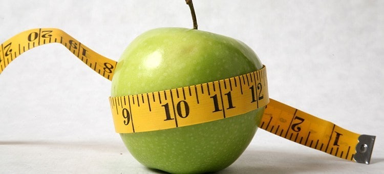 A green apple tied around by a measuring tape.