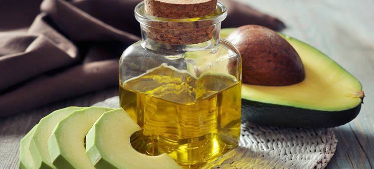 A bottle of avocado oil next to an avocado sliced in half.