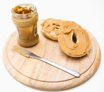 Two bagel slices with peanut butter topping next to a jar of peanut butter and a butterknife.