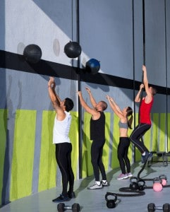 A group of people performing various CrossFit exercises in a gym.