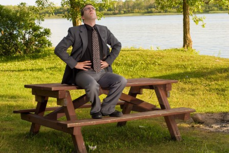 Businessman sitting on a table in a park, taking deep breaths.