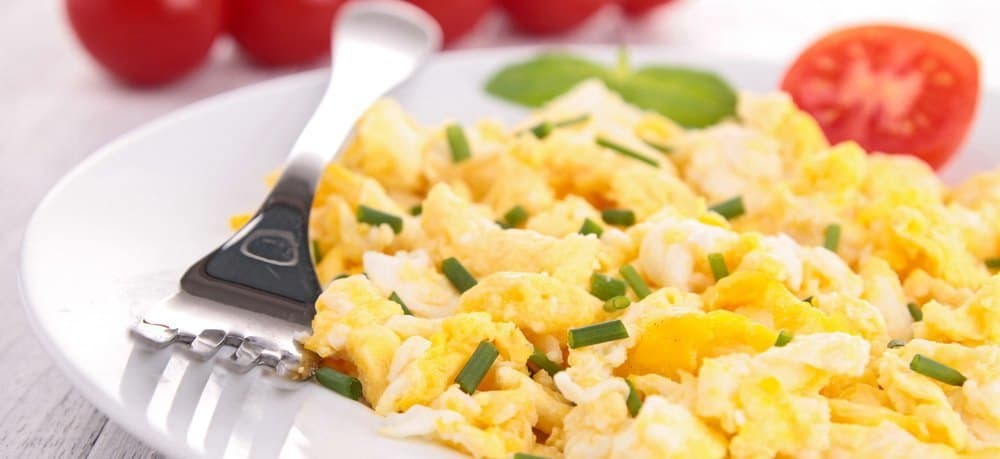 A plate of scrambled eggs with seasoning.