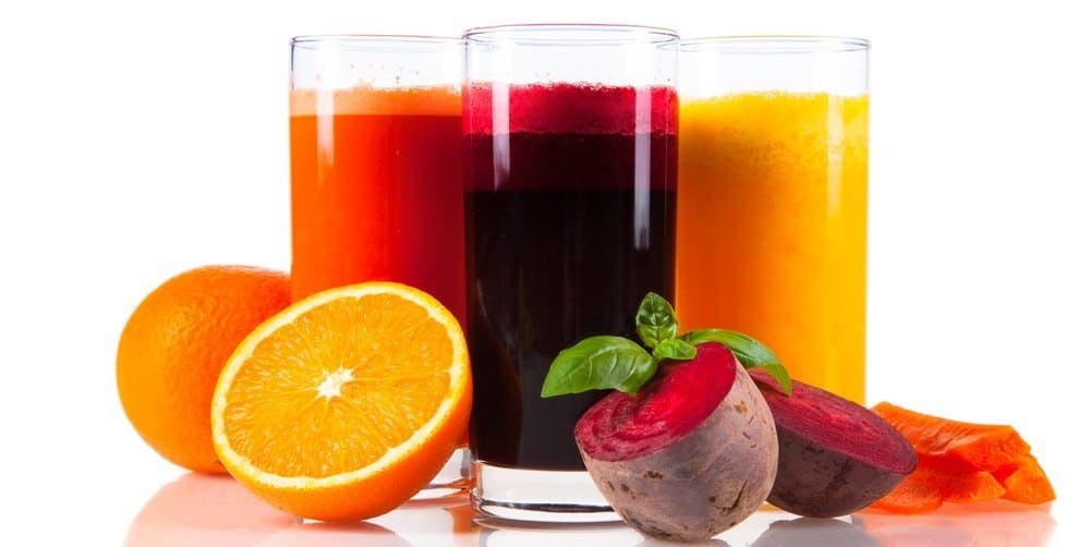 Three glasses of fruit juice with various fruits and vegetables next to them.