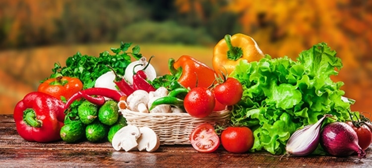 A bunch of healthy vegetables and foods like tomatoes, garlic, peppers, etc laid out on a flat surface.