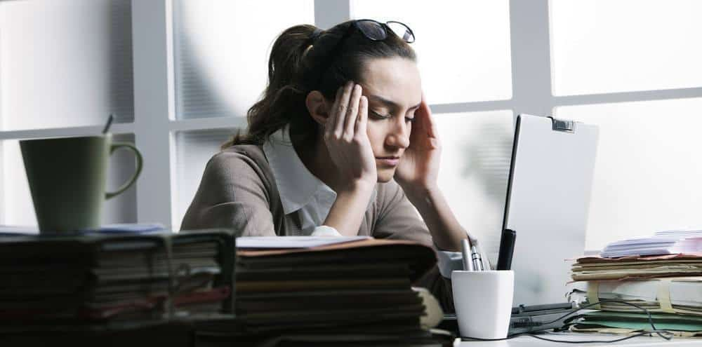 A woman sitting at an office table with a noticeable migraine.