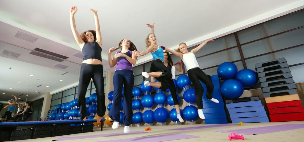 A group of women gleefully jumping up in a gym.