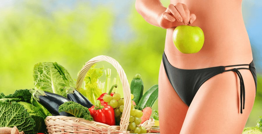 A woman in a bikini holding an apple to her belly, standing next to a basket of various vegetables and fruit.