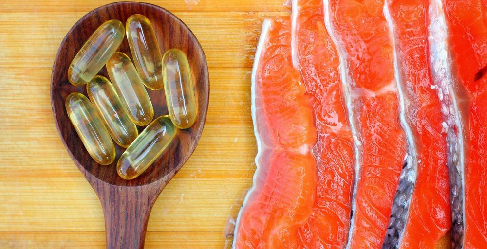 Fish oil capsules in a spoon next to slices of fish.