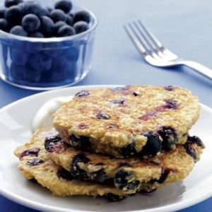 A plate of blueberry pancakes with a bowl of blueberries