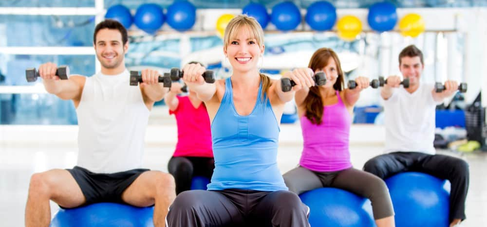 A group of smiling people in a gym performing a pilates exercise using exercise balls and weights.