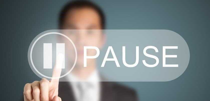 A man pressing the pause button.