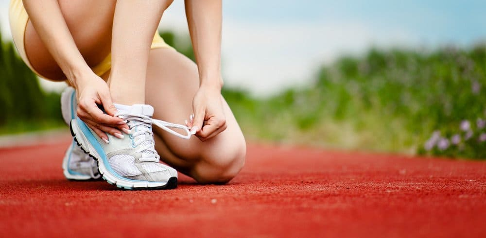 A runner tying her shoe-laces on a track.