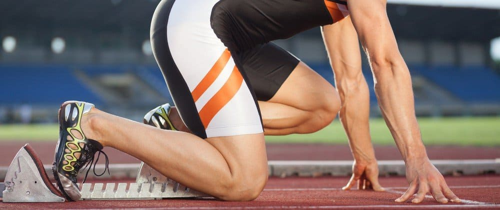 Legs of a sprinter getting ready to run in a stadium.