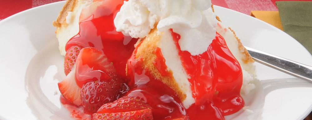 A slice of strawberry shortcake presented on a plate with cream.