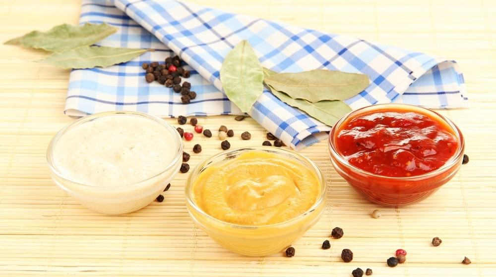A cup of mayonnaise, mustard and ketchup next to a cloth and a few drops of pepper.