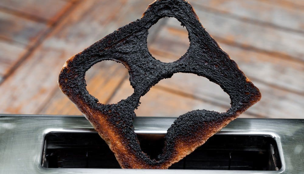 A severely burnt piece of toast with a distraught smiley face carved into it.