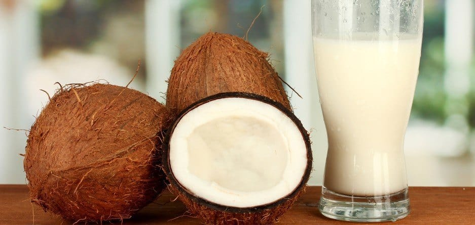 A glass of coconut milk next to coconut shells.