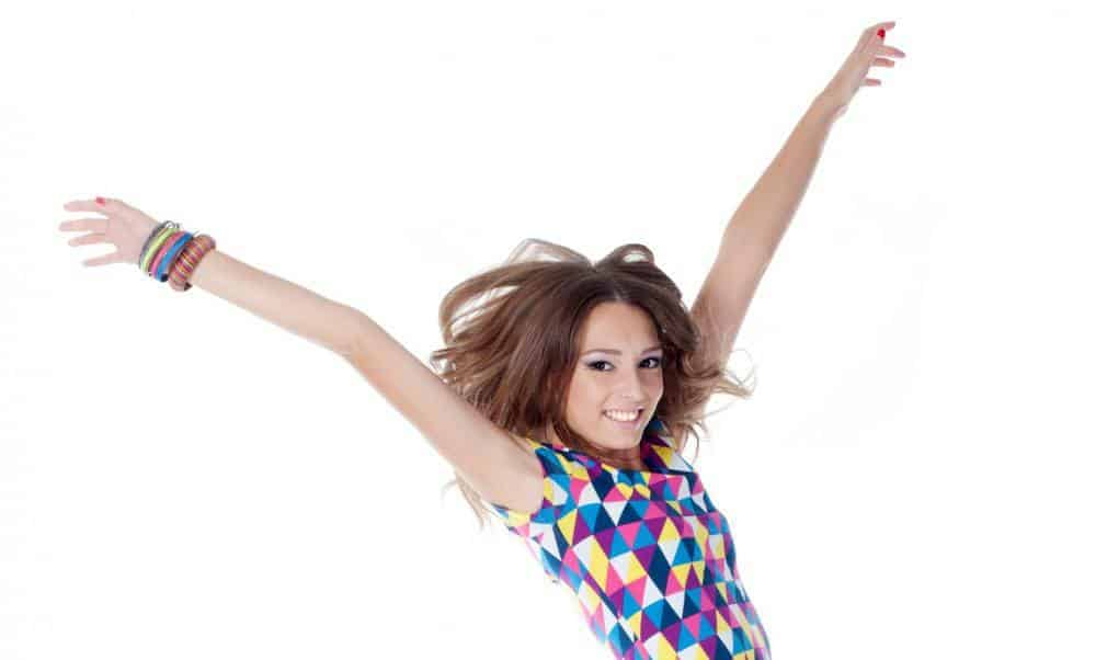 A young woman throwing her arms in the air in joy.