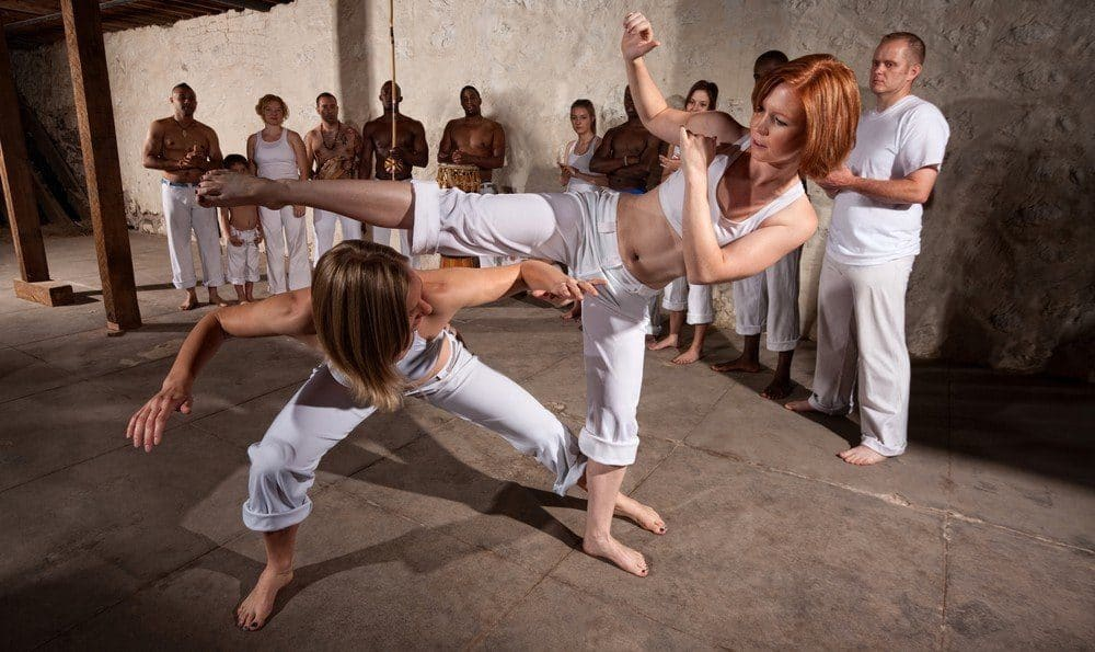Two women sparring during a capoeira session.