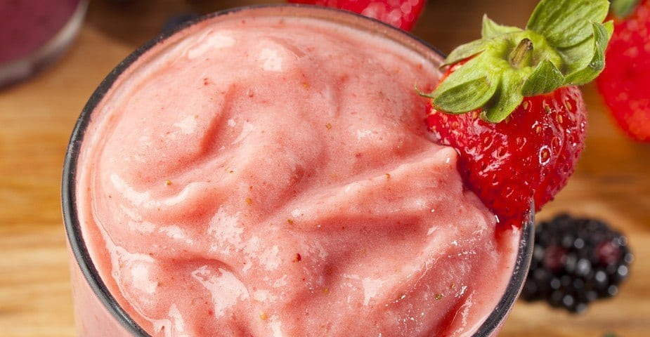 Close-up of a glass of strawberry topped smoothie.