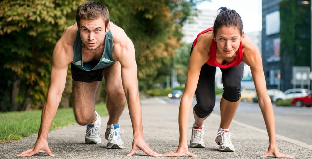 A man and a woman getting ready to run a sprinting race on a suburban or park road