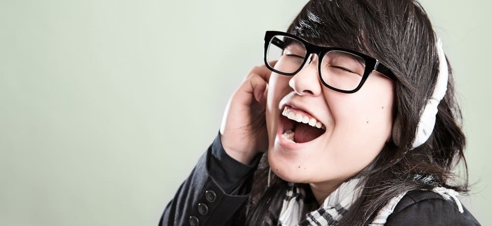 A girl with glasses singing loudly with headphones on.