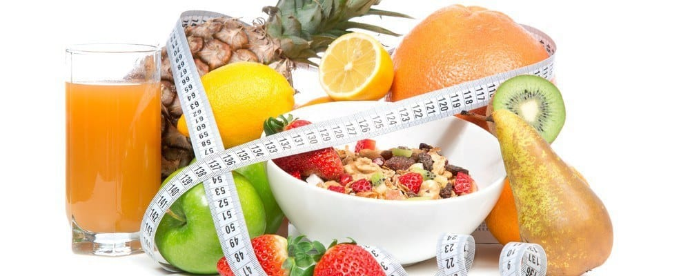 Various healthy foods like fruits, juice, and a bowl of cereal tied around with measuring tape.