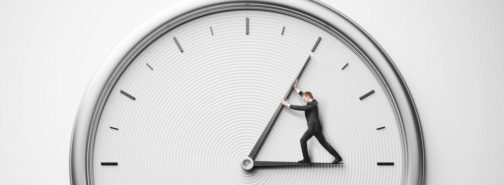 A man struggling to move the hands of a clock towards 12 o'clock.