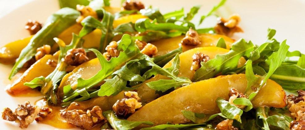 A salad with various ingredients like nuts, fruit, and leafy vegetables.