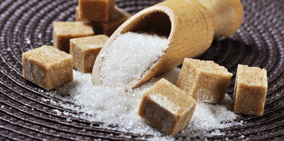 Brown sugar cubes and a spoonful of white sugar.