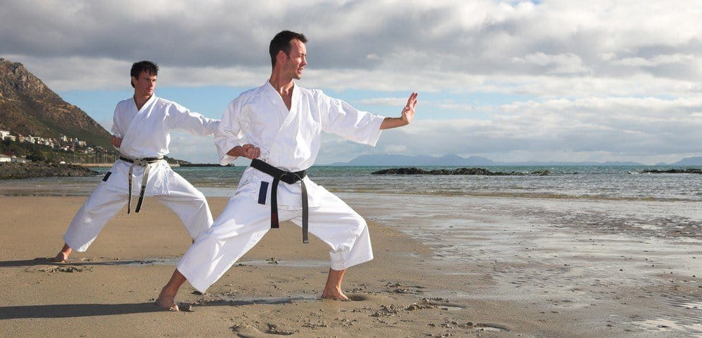 Two people practicing martial arts on a beach.