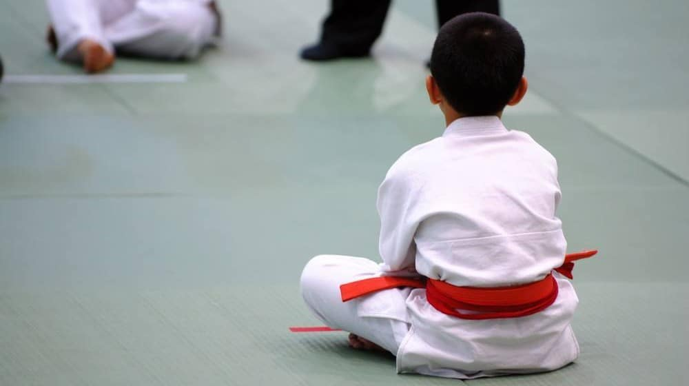 A young boy in a martial arts uniform sitting on the floor during a martial arts event or session.