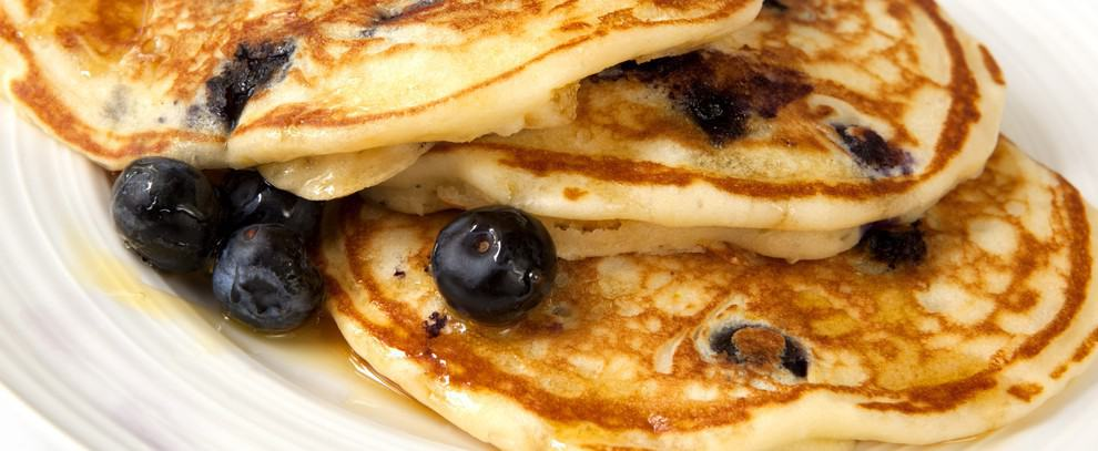 A plate of pancakes with syrup and blueberries.