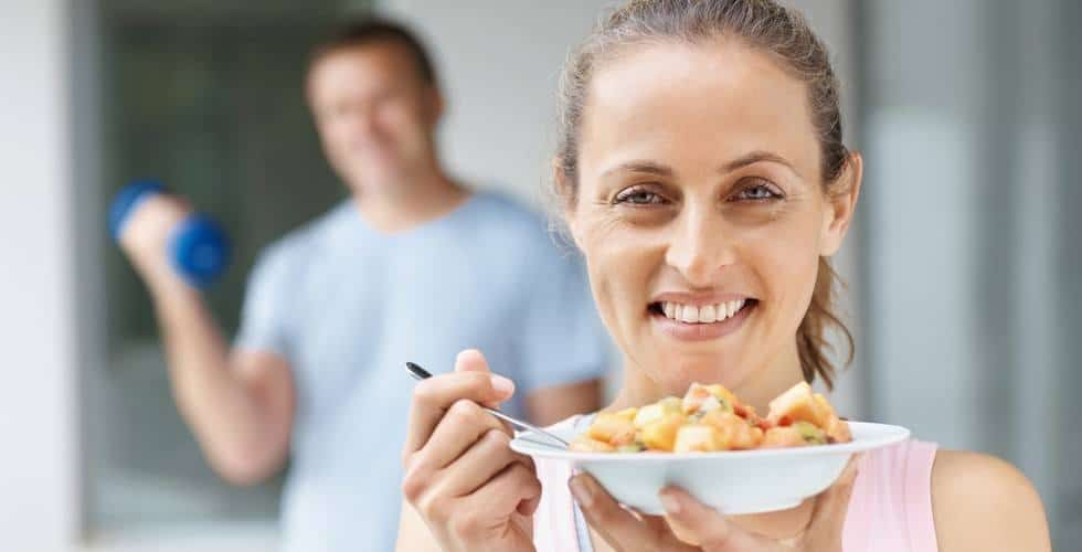 A woman eating a plate of fruit salad with a smiling man lifting weights in the background.