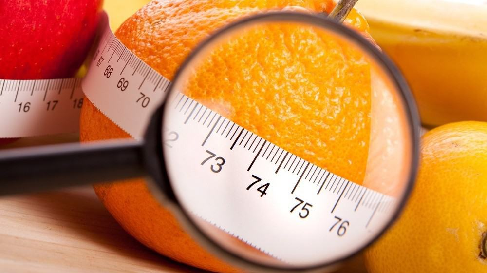 An orange tied with measuring tape and under a magnifying glass.