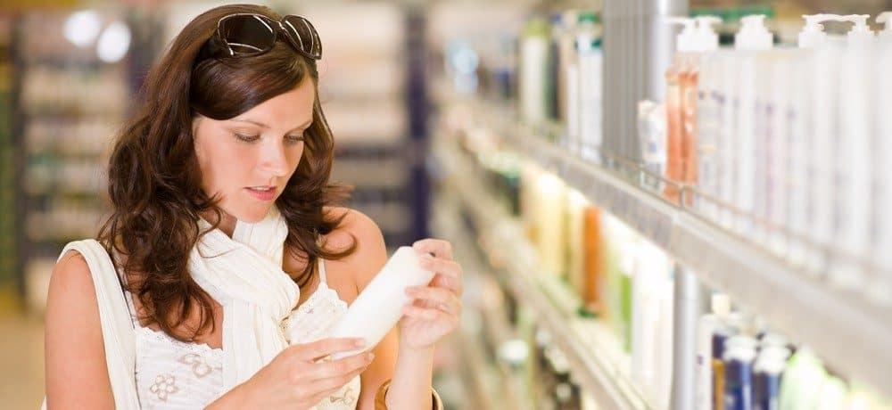 A woman shopping for shampoo in a grocery store, trying to read the label on the bottle.