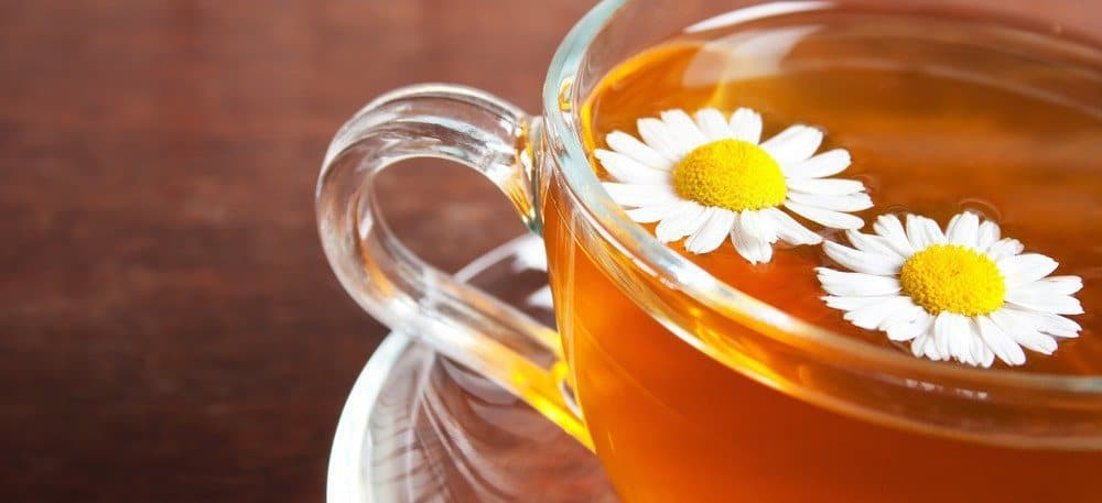 A glass of chamomile tea, with chamomile flowers on top.