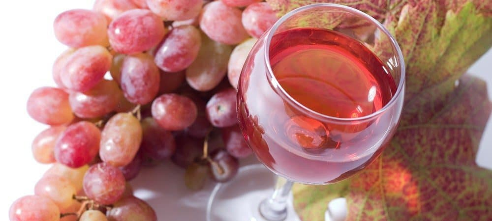 A glass of rose wine next to red grapes.