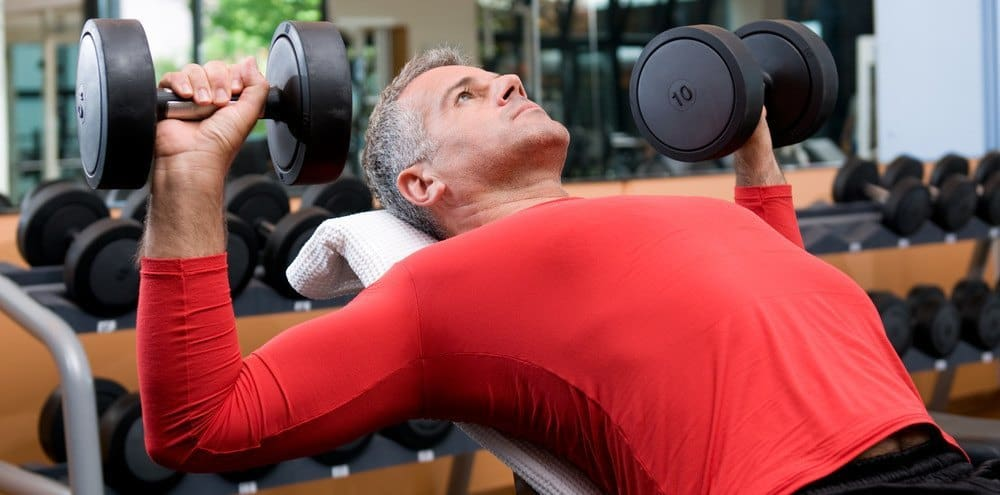 A man in red fitness clothing doing a weightlifting exercise with dumbbells in a gym.