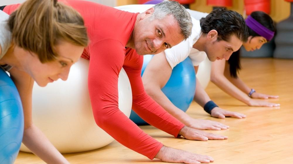 A group of people doing exercises on fitness balls during a fitness session.