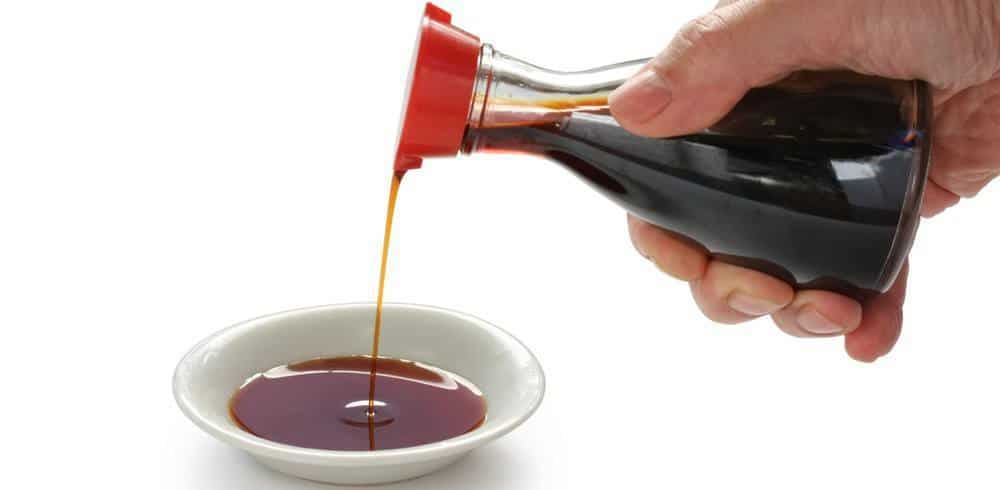 Soy sauce being poured into a small cup.