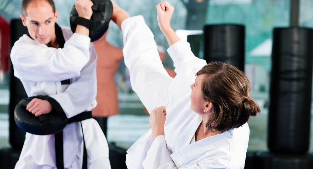 Woman performing a kick during a martial arts training.